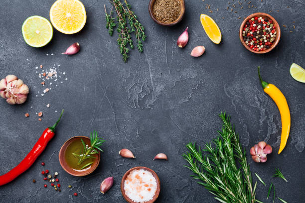 mixed spices and herbs on black stone table top view. ingredients for cooking. food background. - food stock pictures, royalty-free photos & images