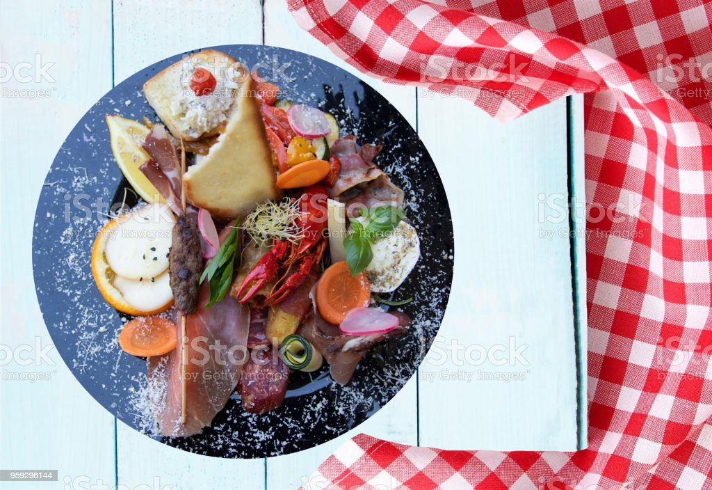 Mixed typical Italian antipasto with ham vegetables and cancer. Concept traditional Italian food. Presented on rustic wooden bright table with red checkered tablecloth. stock photo