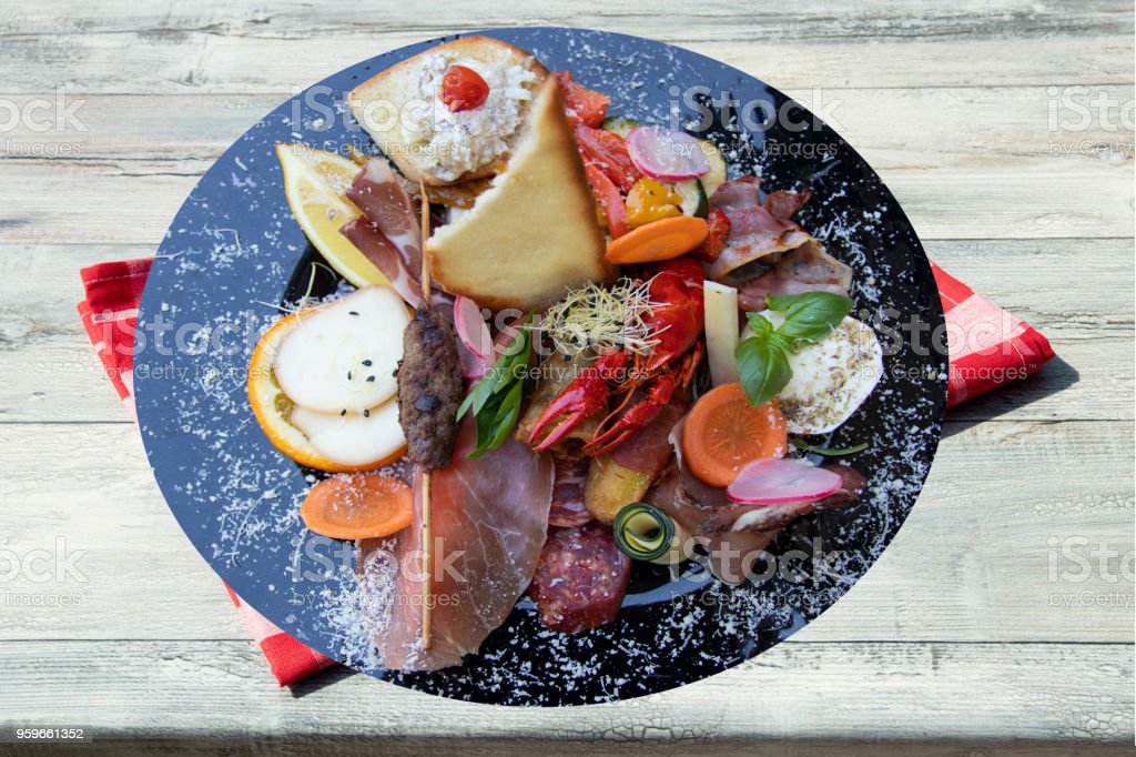 Mixed typical Italian antipasto with ham vegetables and cancer. Concept traditional Italian food. Presented on rustic wooden table with red checkered tablecloth. stock photo