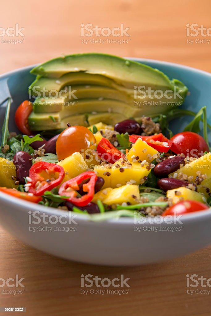 Mixed vegan vegetarian salad in a blue bowl stock photo