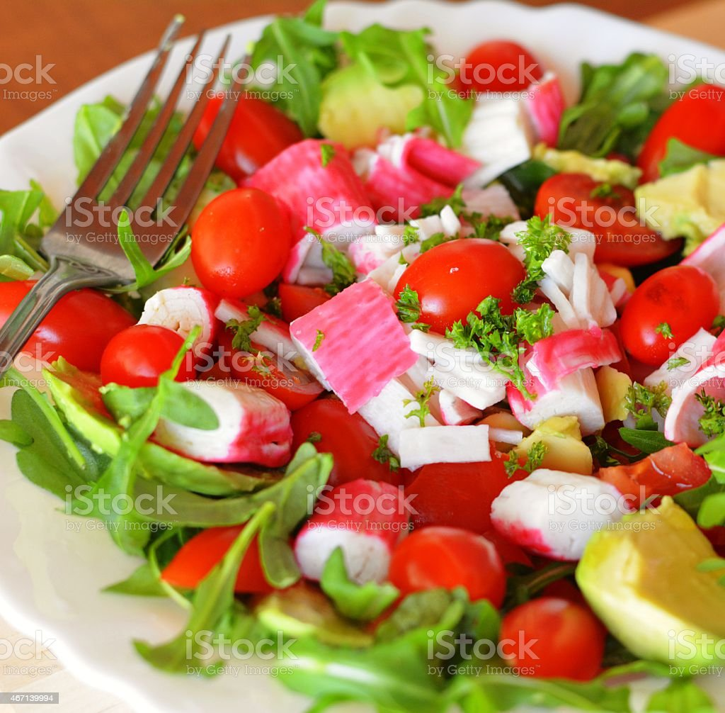 Mixed vegetable salad with crab sticks and avocado stock photo