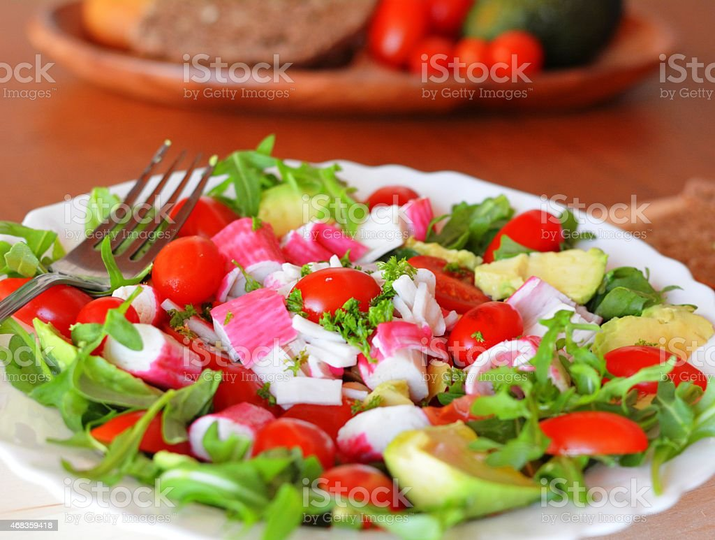 Mixed vegetable salad with crab sticks and avocado royalty-free stock photo