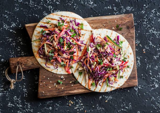 gemischtes gemüse und hühnchen salat tortilla auf einem holzbrett, ansicht von oben. leckerer snack - paprika hähnchen stock-fotos und bilder