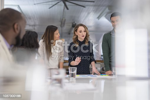 The CEO of a business startup gathers her multiethnic team around the conference table to finalize a product launch. She is signing paperwork and her coworkers are watching next to her.