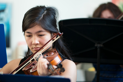 istock Mixed-Ethnic Teenaged Girl Playing Violin in Group Class 1129790068