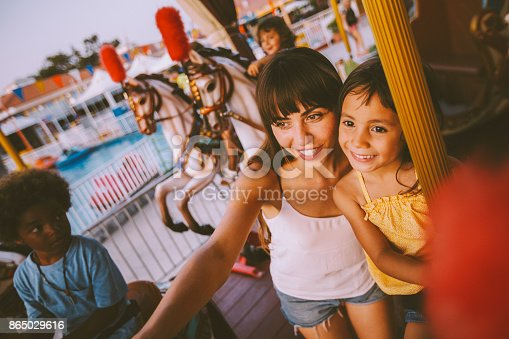 Multi-ethnic family with mother and adopted daughter having fun on amusement park merry-go-round ride