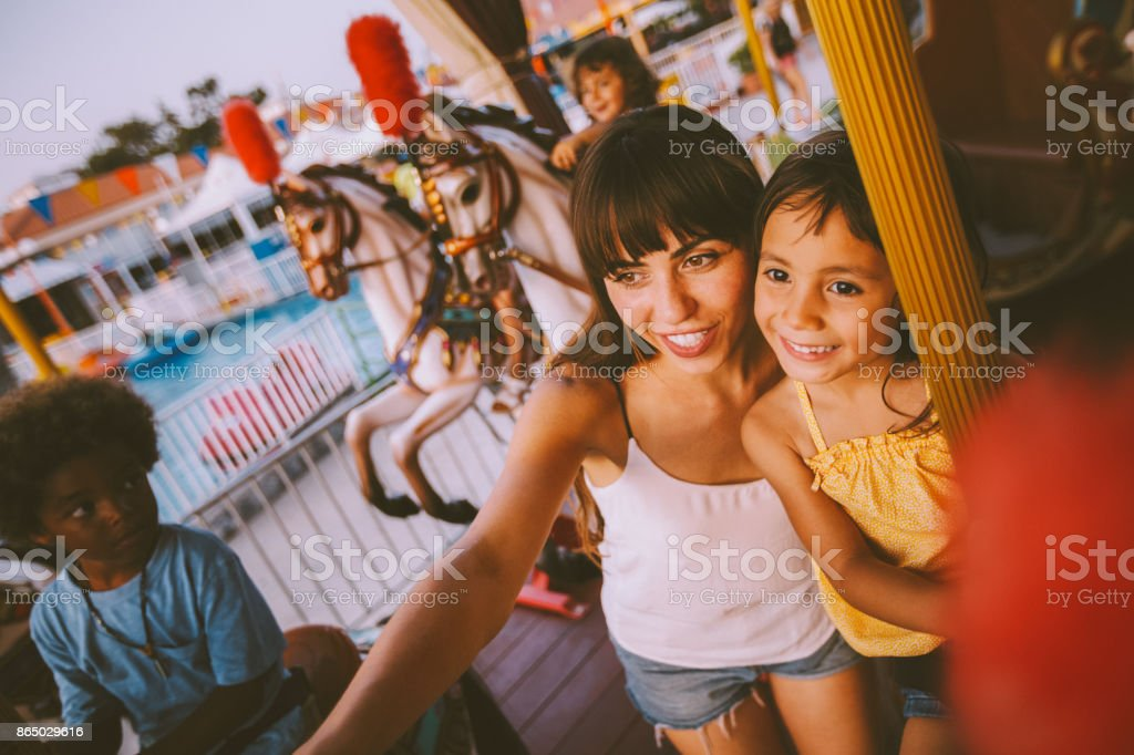 Mixed-race daughter and mother having fun on funfair carousel ride stock photo