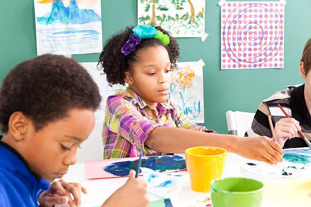 mezclada raza, estudiantes primaria en clase de arte.  pintura con watercolors - clase de arte fotografías e imágenes de stock