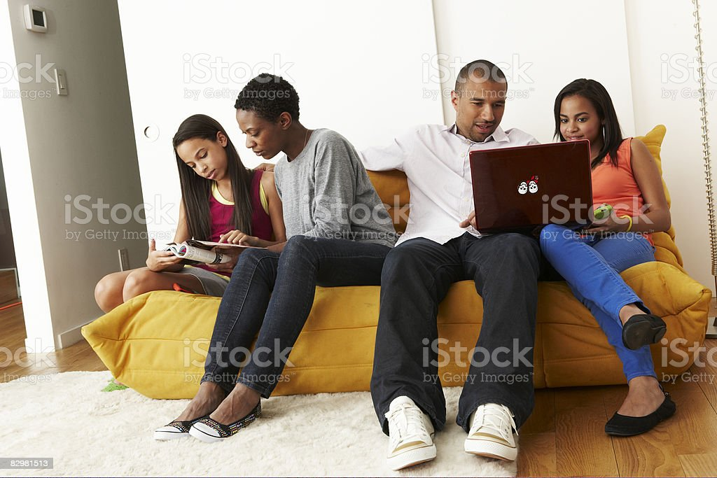 Mixed-race family at home on sofa royaltyfri bildbanksbilder