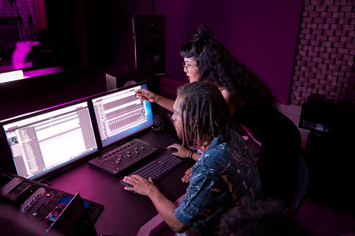 Mixed-race hipster female artist working with african-american male music producer on her song in professional music studio