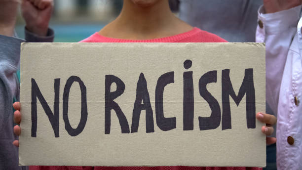 Mixed-race girl holds sign No racism, suffers crowd screaming racial insults Mixed-race girl holds sign No racism, suffers crowd screaming racial insults social justice concept stock pictures, royalty-free photos & images