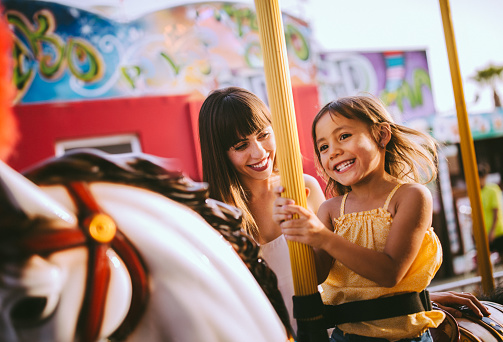 Mixed-race family with daughter and mother having fun on merry-go-round amusement park ride in summer