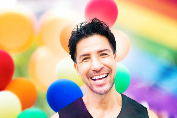 Mixed-race mature man smiling gay pride concept portrait Mixed-race mature man smiling gay pride concept portrait in front of balloons and rainbow colors. gay man stock pictures, royalty-free photos & images