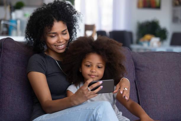 blandad ras mamma och barn flicka ringer videosamtal på mobiltelefon - video call bildbanksfoton och bilder
