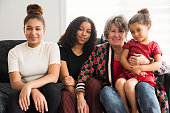 Mixed-race family portrait of grandmother with granddaughters sitting on the living room couch at home. Two teenage daughters and one 4 year's old. They are wearing casual clothes in red, white and black. Horizontal waist up indoors shot with copy space.