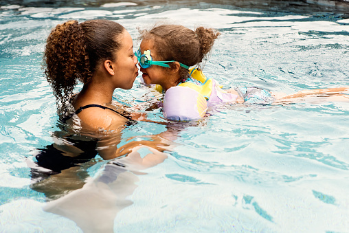 Mixed-race sisters having fun in the backyard pool. From toddler to teenager, they are 3 and 15 year's old. Horizontal full length outdoors shot with copy space.