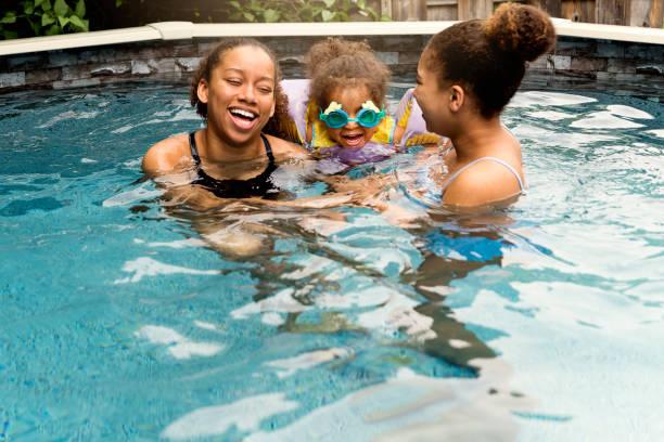 Mixed-race sisters having fun in the backyard pool. stock photo