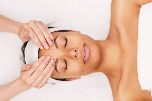 Mixed-Race Woman Enjoying Face Massage in Spa Above view portrait of beautiful mixed-race woman enjoying face massage in luxury spa, copy space massage stock pictures, royalty-free photos & images