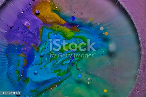 mixing blue yellow and purple color paints on blue background