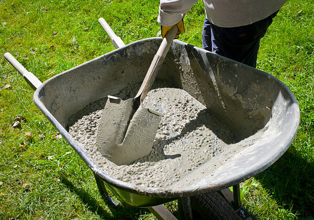 mixing cement by hand in a wheelbarrow. - kruiwagen stockfoto's en -beelden