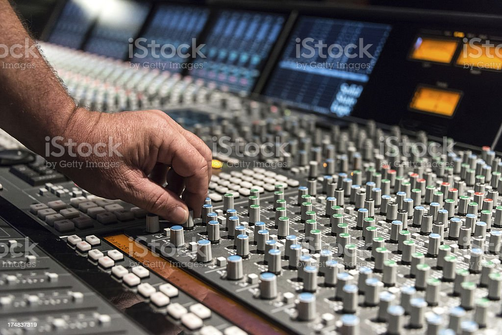 Professional using a recording studio with mixing console.