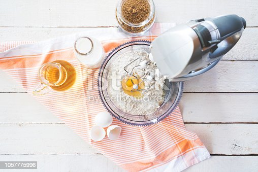 Mixing flour and eggs with a table mixer, ingredients on the table
