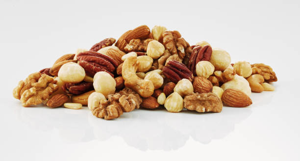 mixing nuts isolated in white background - nuts стоковые фото и изображения