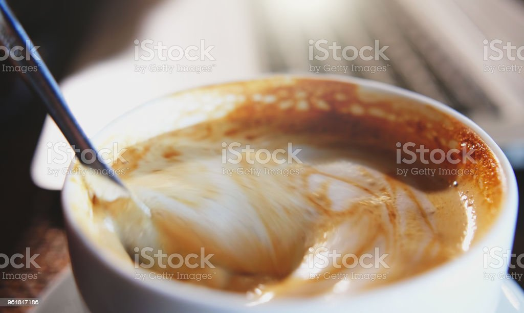 Mixing organic sugars into a cup of latte coffee, slow motion. royalty-free stock photo