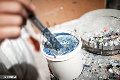 A close-up of a small white plastic bucket being used to mix paint using a stick.