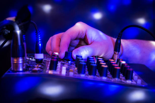 DJ mixing party music on blue background with lights. stock photo
