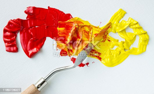 Mixing red and yellow oil paints on a white palette close up