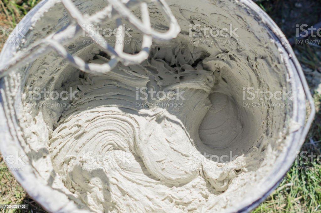 mezcla de adhesivo o cemento con un taladro para trabajos de reparación en obra - foto de stock
