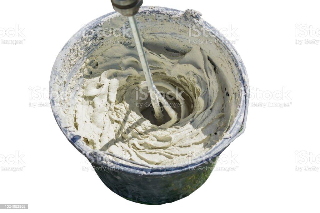 adhesivo o cemento de la mezcla con un taladro para trabajos de reparación aislada sobre fondo blanco - foto de stock