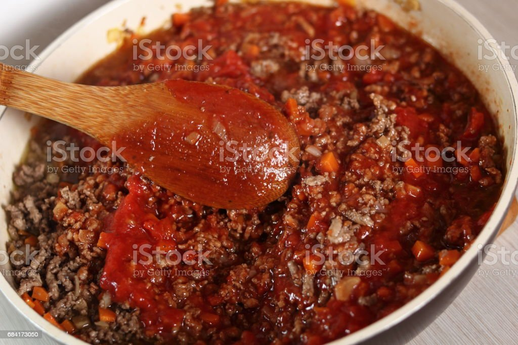 Mixing tomato paste and minced meat. Making Lasagna Bolognese Series. stock photo