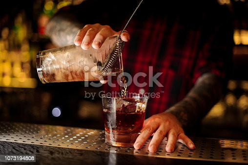 Mixologist pouring fresh strong whiskey cocktail into a glass with an ice cube on the bar
