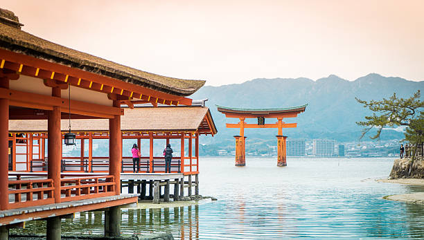 Miyajima Floating Temple Hiroshima, Japan - March 16, 2016: Tourists are taking picture of Miyajima Torii from the corridor of the floating temple. miyajima stock pictures, royalty-free photos & images