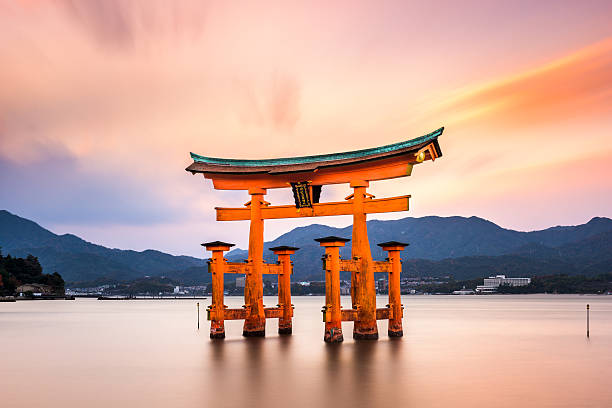 Miyajima Gate in Japan Hiroshima, Japan - December 3, 2015: The floating torii gate of Itsukushima Shrine. The gate, which acts as a boundary between the spirit world and the human world, is said to be 500 to 600 years old. itsukushima shrine stock pictures, royalty-free photos & images
