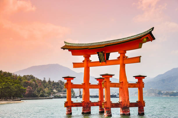 Miyajima, Hiroshima, Japan at the floating gate of Itsukushima Shrine Miyajima, Hiroshima, Japan: April 9, 2011 -The floating gate of Itsukushima Shrine. (gate sign reads Itsukushima Shrine) shinto shrine stock pictures, royalty-free photos & images