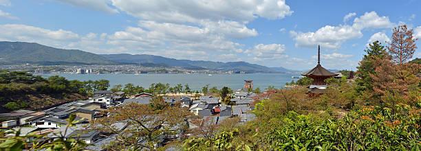 Miyajima Island and Hiroshima, Japan Panoramic view of the Miyajima Island with Hiroshima suburbs in the background, behind Onoseto Strait. miyajima stock pictures, royalty-free photos & images