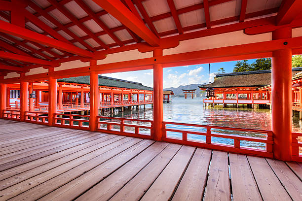 Miyajima Shrine Japan Hiroshima, Japan - December 3, 2015: The open air halls of Itsukushima Shrine on Miyajima Island. The shrine is known for the famous floating torii gate seen in the distance. itsukushima shrine stock pictures, royalty-free photos & images