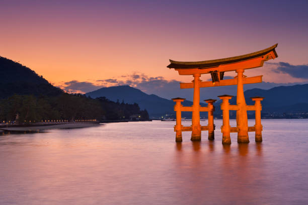 Miyajima torii gate near Hiroshima, Japan at sunset Miyajima, Japan - November 14, 2014: The torii gate of the Itsukushima Shrine on Miyajima Island near Hiroshima. A gate has been in place since 1168, the current gate dates back to 1875. hiroshima prefecture stock pictures, royalty-free photos & images