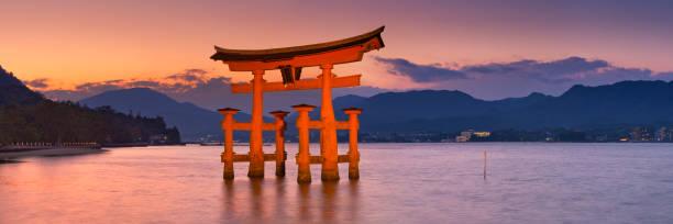 Miyajima torii gate near Hiroshima, Japan at sunset Miyajima, Japan - November 14, 2014: The torii gate of the Itsukushima Shrine on Miyajima Island near Hiroshima. A gate has been in place since 1168, the current gate dates back to 1875. miyajima stock pictures, royalty-free photos & images
