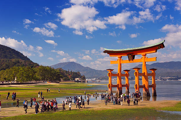 Miyajima torii gate, near Hiroshima, Japan Miyajima, Japan - November 15, 2014: People walking up to the torii gate of the Itsukushima Shrine at low tide. A gate has been in place on Miyajima Island since 1168, the current gate dates back to 1875. itsukushima shrine stock pictures, royalty-free photos & images