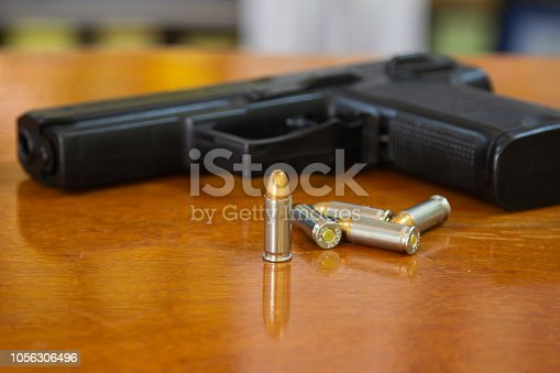 istock .38 mm handgun and bullets strewn on the rustic wooden table background. Gun with ammunition and isolated ammo or 9mm handgun on wood surface at home. Protect property refers to serious social issues 1056306496