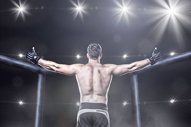 mma fighter in arena celebrating win, behind view - combat sport stock pictures, royalty-free photos & images