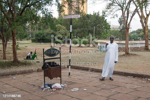 NAIROBI, KENYA - MARCH 4 2012: Unidentified man smokes cigarette in smoking zone of Uhuru Park in Nairobi, Kenya. Uhuru Park is a recreational city park adjacent to central district of Nairobi.