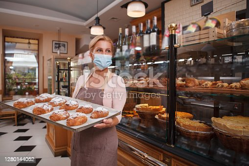 istock MMature femmale baker working at her shop 1280144052