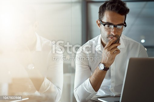 Cropped shot of a handsome young businessman looking thoughtful while working on his laptop in the office