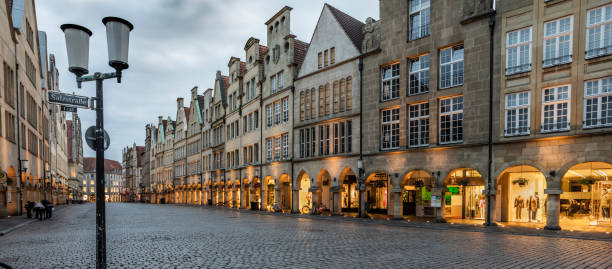Münster in Germany Gallery with arcades on the Prinzipalmarkt in Münster ,shaped by historic buildings  The Prinzipalmarkt is the historic principal marketplace of Münster, Germany. Shot at dusk. Buildings already illuminated. north rhine westphalia stock pictures, royalty-free photos & images