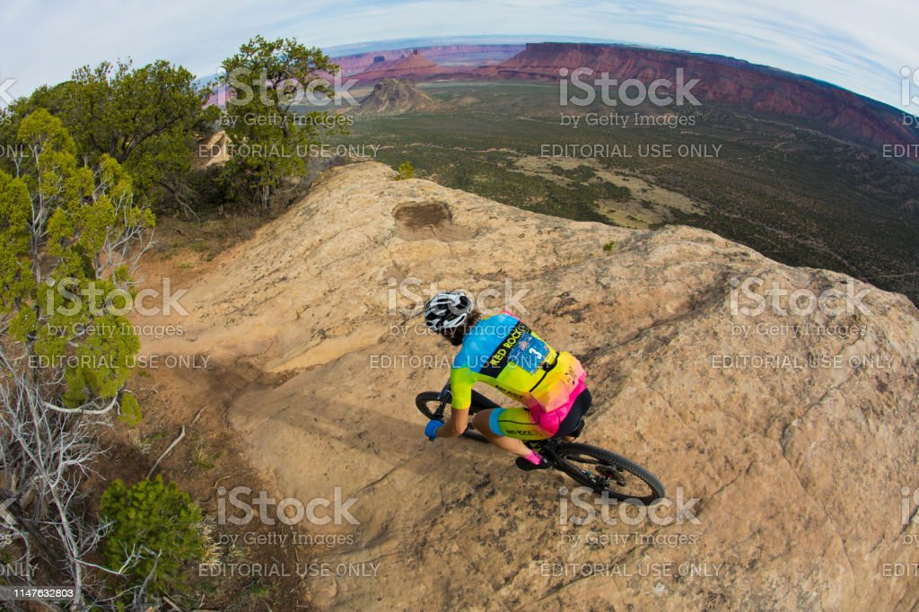 A male cyclist rides along the edge of Porcupine Rim while competing...